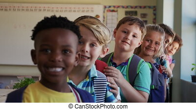 Group of kids standing in a queue in school - Portrait of ...