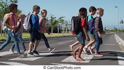 Group of kids with school bags crossing the road - Multi-...