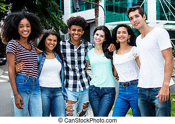 Group of laughing international young adult people in city