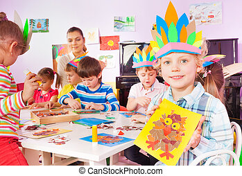 Group of little children glue and draw in class