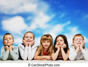 Group of little children lying in a row against blue sky
