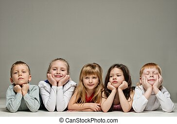 Group of little children lying in a row isolated on grey