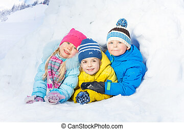 Group of little kids play in snow igloo