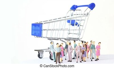 Group of little toy men and women stand in front of shopping trolley