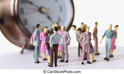 Group of little toy men and women stand in front of big clock