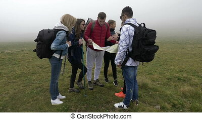 Group of lost young tourists hiking looking for direction...