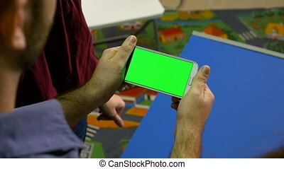 Group of man and woman watching smart phone with green screen and pointing at something