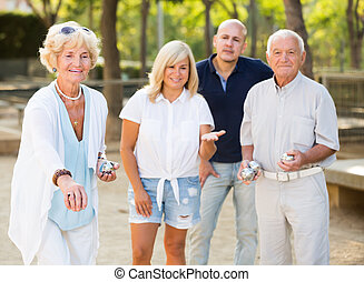Group of mature friends playing petanque in park