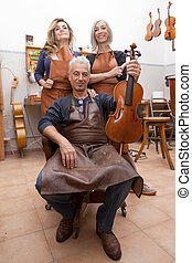 group of mature violin maker in pose while testing the...