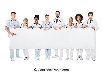 Group Of Medical Team Holding Blank Billboard