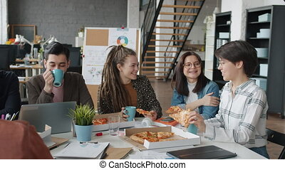 Group of happy men and women are eating pizza talking and laughing in open space office enjoying lunch break together. People and workplace concept.