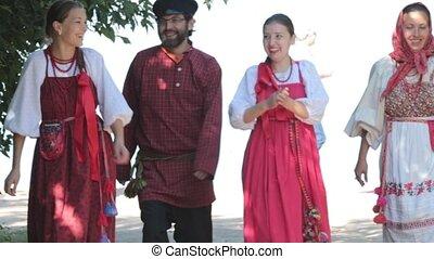 Group of men and women walking in russian folk costumes in...