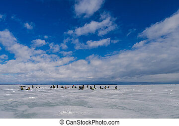 group of men fishermen fishing in winter on the ice of the river