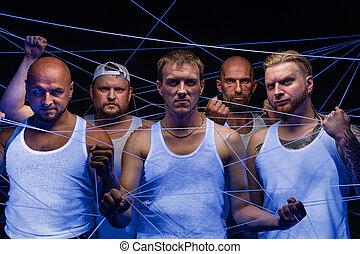 Group of men tangled in threads in neon light
