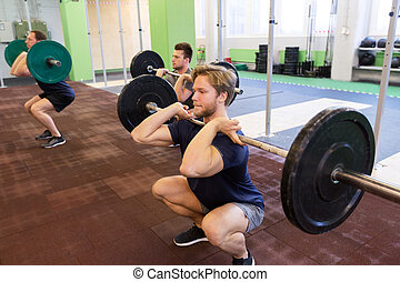 group of men training with barbells in gym