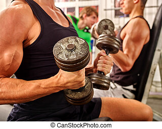 Group of men working with dumbbells  at gym.