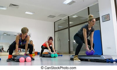 Group of middle age women at the gym doing working out session at the stepper