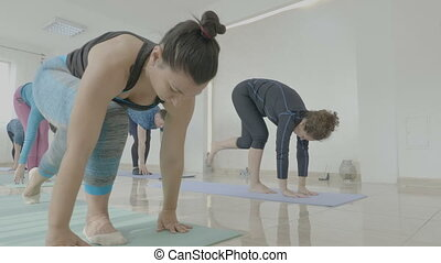 Group of middle aged women toning their bodies during a yoga class session in a fitness studio