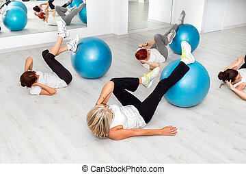 Group of middle aged women working out with fitness balls.