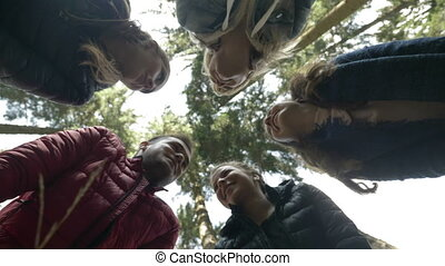 Group of millennials in the forest placing their hands in a circle celebrating success and motivational business trip