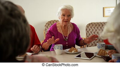 Group of Mixed-race senior friends eating breakfast on ...