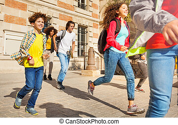 Group of mixed race teens running after classes