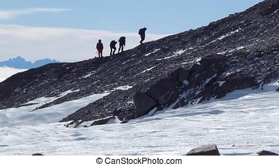 Group of mountain backpackers walking on snow. Climb to mountain. Walking in the mountains