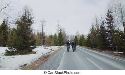 Group of mountain bikers riding on road outdoors in winter,...
