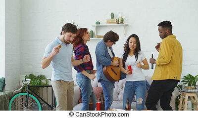 Group of multi ethnic friends dancing and playing guitar while have home party indoors