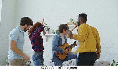 Group of multi ethnic friends dancing while young man playing guitar and having home party indoors