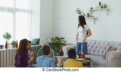 Group of multi-ethnic friends having fun playing party game at home. Young asian girl showing something or somebody and her flatmates trying to guess it