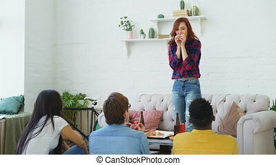 Group of multi-ethnic friends having fun playing party game at home indoors. Young girl showing something or somebody and her flatmates trying to guess it