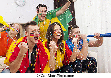 Group of multi-ethnic people celebrates win of favourite football team