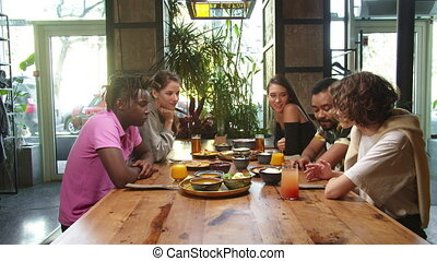 Group of multicultural friends sit at lunch and talk