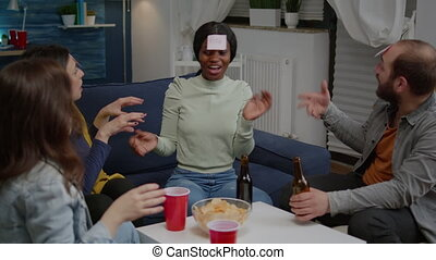 Group of multiethnic friends with sticky notes putting on forehead playing guess who game during home party. Mixed race people having fun, laughing together while sitting on sofa late at night