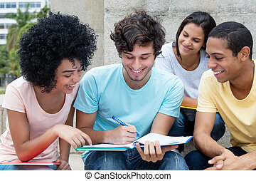 Group of multiethnic students learning outdoors on campus in...