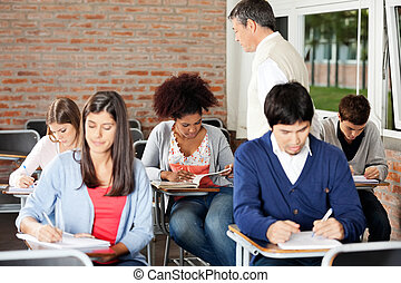 Group of multiethnic students writing exam while teacher supervising them in classroom