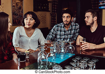 Group of multiracial friends resting and talking at bar or pub.