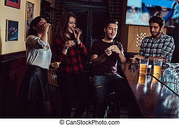 Group of multiracial friends resting and talking at the bar or pub.