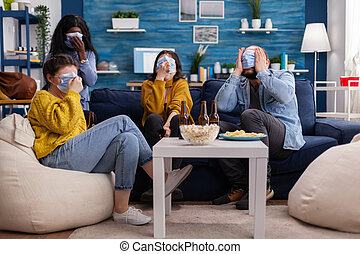 Group of multiracial friends watching horror show on tv