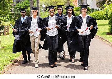 group of multiracial graduates walking on campus