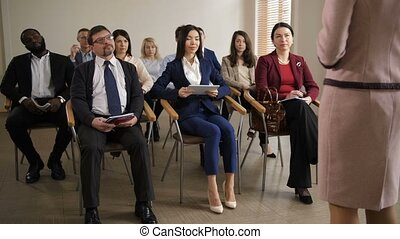 Group of multiracial listeners at business seminar -...