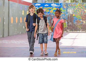 Group of multiracial schoolmates walking and smiling
