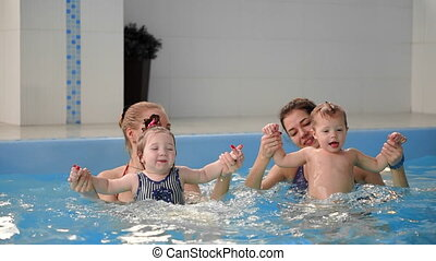 Group of mums with their baby children at infant swimming...