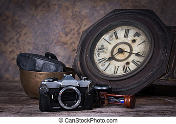 Group of objects on wood table. antique wooden clock, hourglass, old camera ,Still life