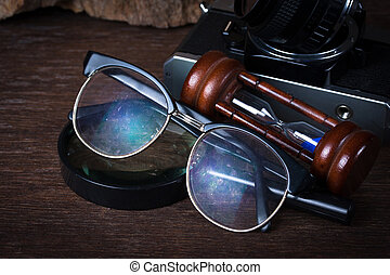 Group of objects on wood table.  glasses, hourglass,old camera,