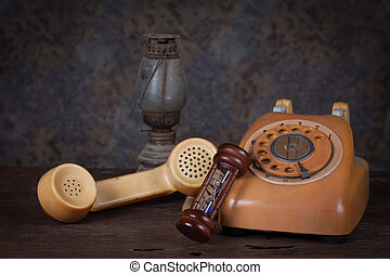 Group of objects on wood table.  hourglass, old  telephone, old rusty kerosene lamp