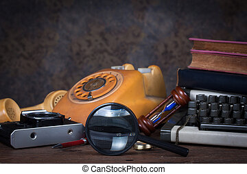 Group of objects on wood table. magnifying glass, old telephone, type writer, old camera, Still life