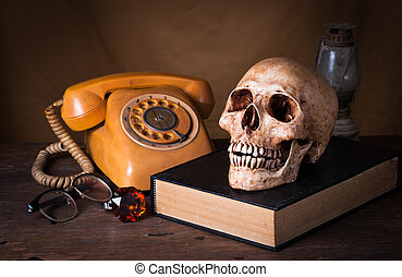 Group of objects on wood table. old book, human skull ,old rusty kerosene lamp, old telephone, Still life