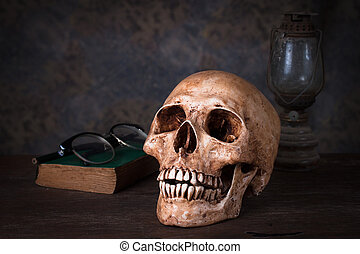 Group of objects on wood table. old book, human skull ,old rusty kerosene lamp, Still life